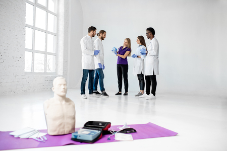 Group of young medics standing and talking together during the break of the first aid training with medical stuff and dummies on the floor Archivio Fotografico - 113403115