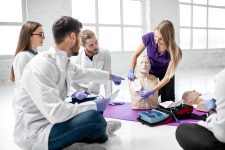 Un groupe de jeunes médecins avec instructeur montre comment effectuer une défibrillation sur le mannequin pendant la formation aux premiers secours à l'intérieur Banque d'images
