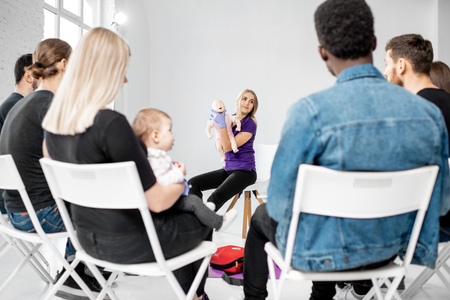 Group of people during the training with instructor showing on baby dummy how to provide first aid to the suffocating child Stock Photo