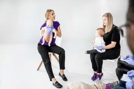 Young mother with baby during the first aid training with instructor showing on baby dummy how to help to the suffocating child Stock Photo