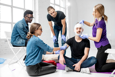 Group of young people during the first aid training with instructor showing how to tie a bandage on the head of injured person Stock Photo