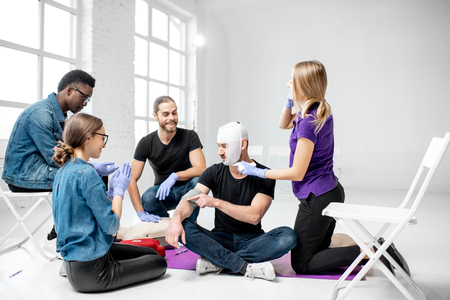 Group of young people during the first aid training with instructor showing how to tie a bandage on the head of injured person 版權商用圖片