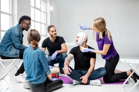 Group of young people during the first aid training with instructor showing how to tie a bandage on the head of injured person Stockfoto