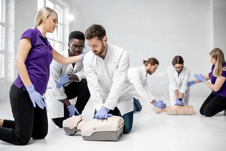 Groupe de jeunes médecins pratiquant la respiration artificielle avec des mannequins médicaux pendant la formation aux premiers secours dans la salle blanche