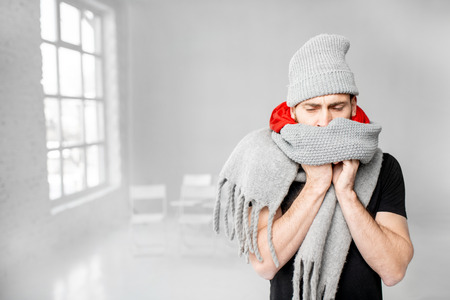 Portrait of a man wrapped in a warm scarves and hat feeling bad having a winter disease indoors