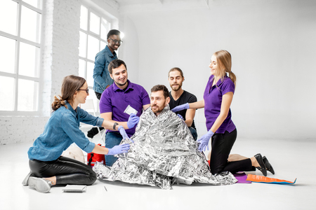 People during the first aid training with instructors and man as injured person covered in thermal blanket indoors