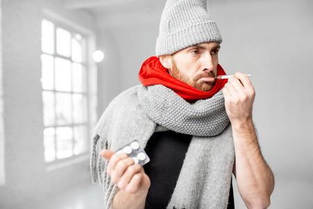 Portrait of a man wrapped in a warm scarves and hat feeling bad measuring body temperature indoors. Winter disease concept Stockfoto - 113403854