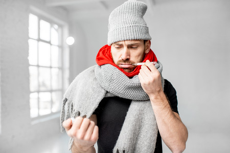 Portrait of a man wrapped in a warm scarves and hat feeling bad measuring body temperature indoors. Winter disease concept Stockfoto - 113403861