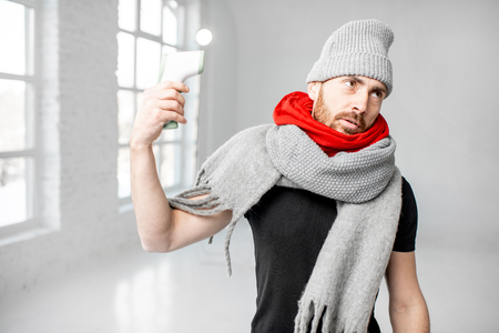 Portrait of a man wrapped in a warm scarves and hat feeling bad measuring body temperature with electronic thermometer indoors