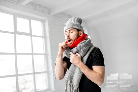 Portrait of a man wrapped in a warm scarves and hat feeling bad having a winter disease indoors Stockfoto - 113403871