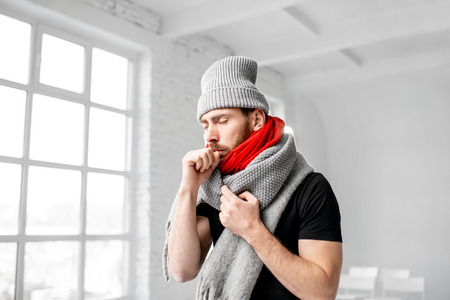 Portrait of a man wrapped in a warm scarves and hat feeling bad having a winter disease indoors Stockfoto - 113403873