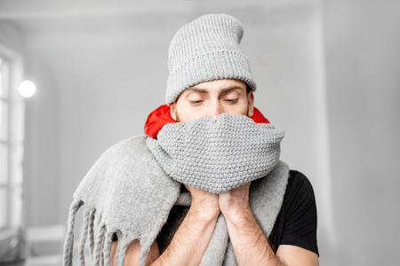 Portrait of a man wrapped in a warm scarves and hat feeling bad having a winter disease indoors Stockfoto - 113403893