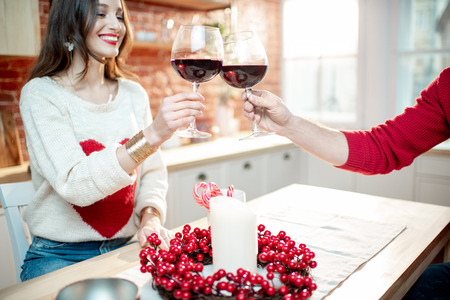 Young couple celebrating New Year clinking with wine glasses in the kitchen of their decorated apartment, close-up view Stock Photo
