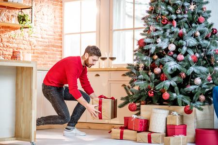 Hombre poniendo regalos bajo el árbol de Navidad preparándose para unas vacaciones de año nuevo en casa