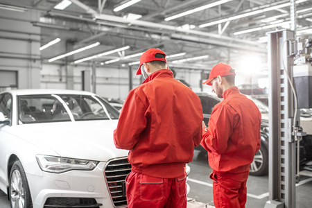 Two auto mechanics in red uniform standing together in front of the luxury car at the car service