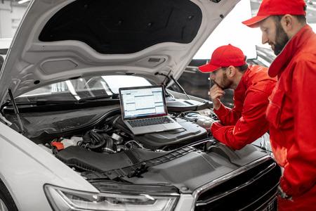 Due meccanici in uniforme rossa che eseguono la diagnostica del motore con il computer nel servizio dell'auto
