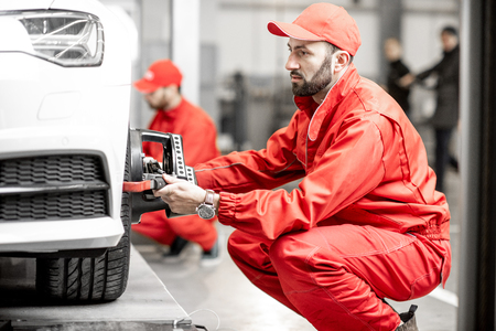 Two auto mechanics in red uniform fixing disk for wheel alignment on a luxury car at the car service Stock Photo