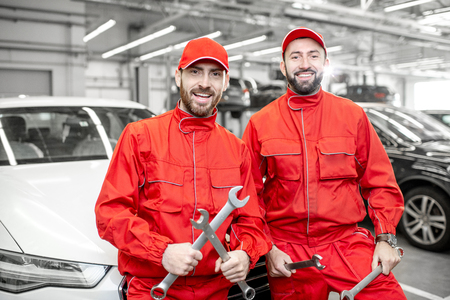Portrait of a two handsome auto mechanics in red uniform standing with wrenches at the car service