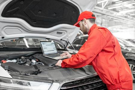 Mecánico de automóviles guapo en uniforme rojo haciendo diagnósticos de motor con computadora en el servicio de automóviles