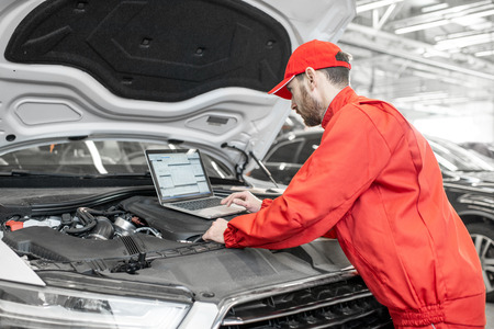 Przystojny mechanik samochodowy w czerwonym mundurze przeprowadzający diagnostykę silnika za pomocą komputera w serwisie samochodowym