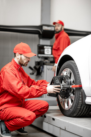 Handsome auto mechanic in red uniform fixing disk for wheel alignment at the car service