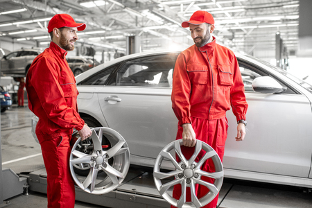 Two male auto mechanics in red uniform walking with alloyed wheels at the car service Zdjęcie Seryjne