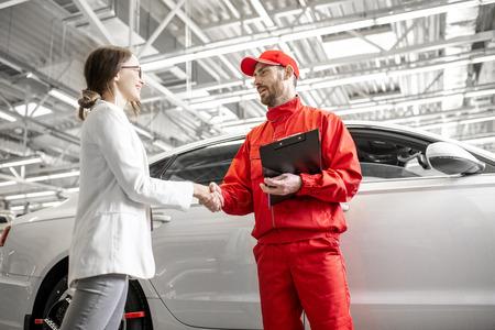 Młoda kobieta klient uścisk dłoni z mechanikiem samochodowym w czerwonym mundurze mającym umowę w serwisie samochodowym