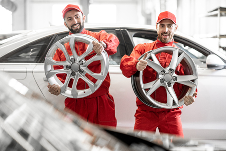 Funny portrait of a two auto mechanics in red uniform with alloyed wheels at the car service Stock Photo
