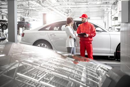 Młoda kobieta klient z mechanikiem samochodowym w czerwonym mundurze w serwisie samochodowym. Szeroki kąt widzenia z miejscem na kopię
