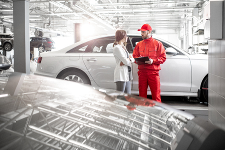 Young woman client with auto mechanic in red uniform at the car service. Wide angle view with copy space