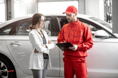 Jonge vrouw cliënt met automonteur in rood uniform staande met enkele documenten bij de autoservice