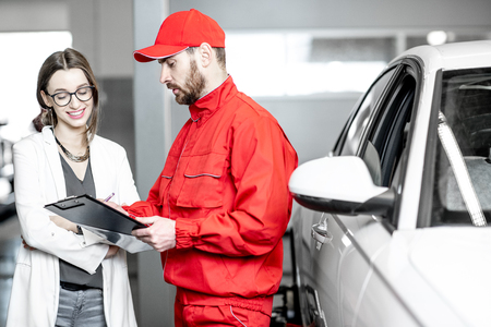 Young woman client with auto mechanic in red uniform standing with some documents at the car service Фото со стока