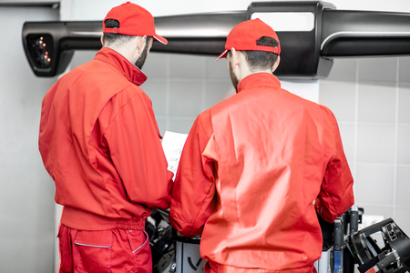 Auto mechanics in red uniform working with computer doing wheel allignment at the car service