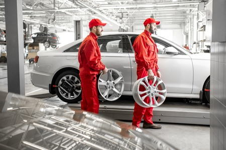 Two male auto mechanics in red uniform walking with alloyed wheels at the car service 写真素材