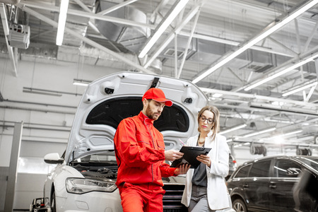 Young woman client with auto mechanic in red uniform standing with some documents at the car service. Wide view with copy space
