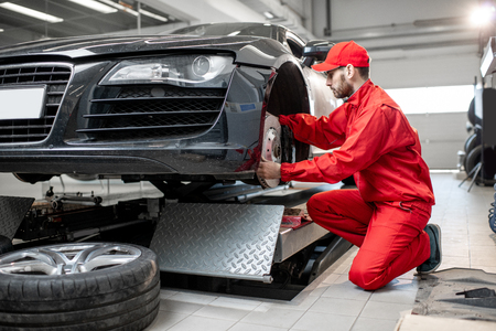 Auto mechanic in red uniform servicing sports car checking front brakes in the car service Archivio Fotografico