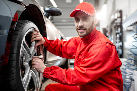 Portrait of a car service worker in red uniform changing wheel of a sport car at the tire mounting service Фото со стока