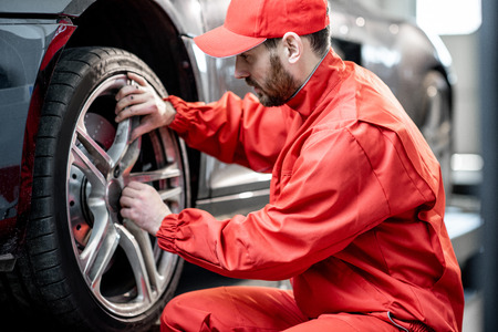Car service worker in red uniform changing wheel of a sport car at the tire mounting service 스톡 콘텐츠