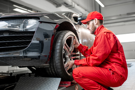 Car service worker in red uniform changing wheel of a sport car at the tire mounting service Stock Photo