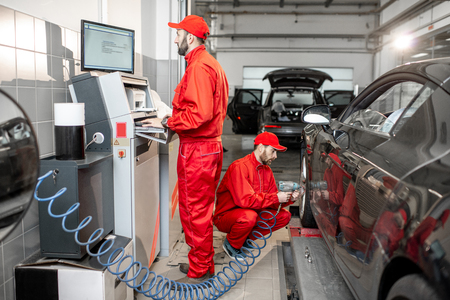 Car service workers in red uniform balancing and changing wheels of a sport car at the tire mounting service Stok Fotoğraf