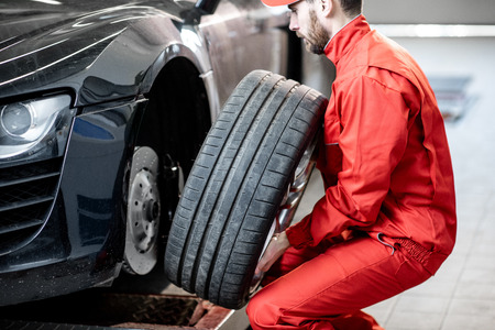 Car service worker in red uniform changing wheel of a sport car at the tire mounting service Stok Fotoğraf