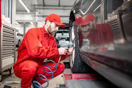 ar service worker in red uniform changing wheel of a sport car at the tire mounting service