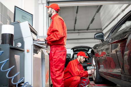 Car service workers in red uniform balancing and changing wheels of a sport car at the tire mounting service Stock Photo