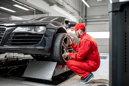 Car service worker in red uniform changing wheel of a sport car at the tire mounting service