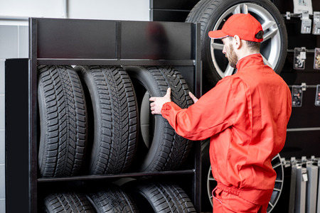 Car service worker in red uniform taking new wheel from the shelves of the wheel store 스톡 콘텐츠 - 114134287