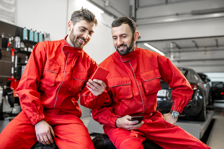 Car service workers in red uniform having a break sitting together with phone on the wheels at the tire mounting service 스톡 콘텐츠