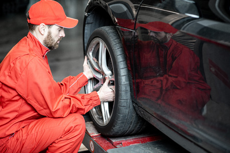 Car service worker in red uniform changing wheel of a sport car at the tire mounting service Фото со стока