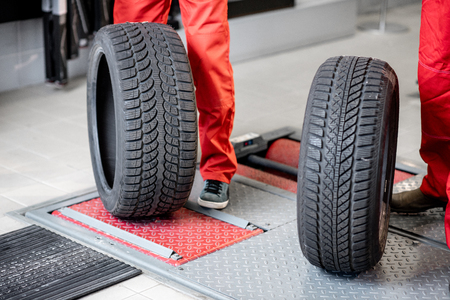 Worker in uniform carrying new tires at the car service or store, close-up view