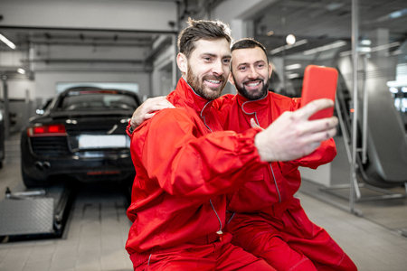 Car service workers in red uniform making selfie photo with phone during a break at the tire mounting service