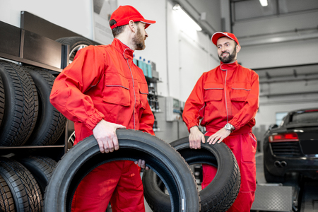 Car service workers in red uniform carrying new tires at the tire mounting service or shop